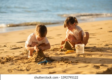 Brother and sister playing together with beach toys