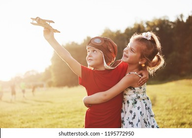 Brother and sister are playing together. Two children playing with a wooden airplane outdoor.