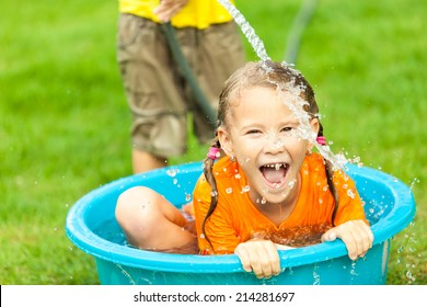 brother and sister playing with water near a house at the day time