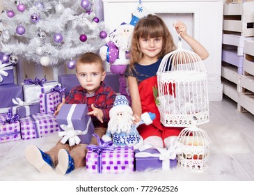 Brother and sister print presents decorate the Christmas tree indoors. Loving family close up. Stylish haircut. Cute child.