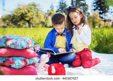 brother and sister read a book on picnic