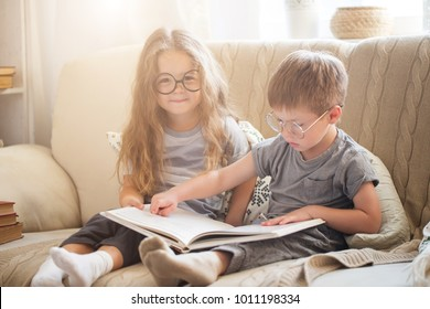 Brother and sister reading a book on the sofa