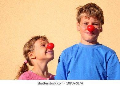 Brother and sister with red clown noses stand near wall and smiles. Girl looks at boy.