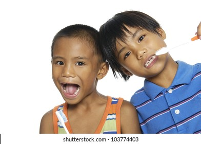 Brother and sister in same shirts brush their teeth on white background. Close-up