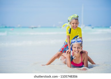 Brother and sister in scuba masks playing and having fun on the beach during the hot summer vacation day.