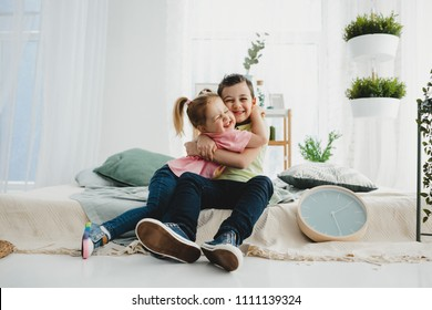 Brother and sister sit hugging on the bed
