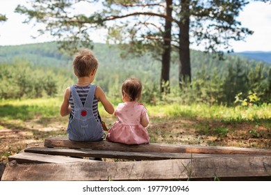 Brother and sister sit with their backs turned on wooden boards and logs on a sunny summer day in a pine forest. A boy in overalls, a girl in a summer pink dress