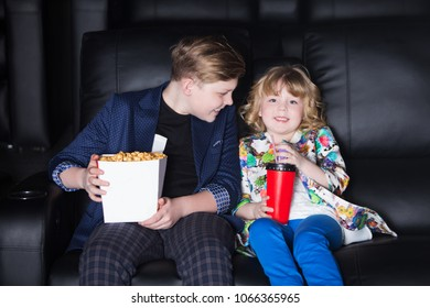 Brother and sister sitting at the cinema, watching a film and eating popcorn. movie theater.