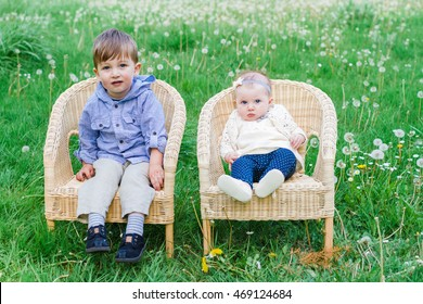 Brother and sister sitting next to each other outdoors in chairs with natural lighting.