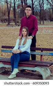 Brother and sister sitting on a bench in the park.