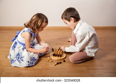 Brother and sister sitting on the floor and playing a board game