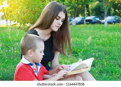 A brother and sister are sitting on the green grass and reading a book.