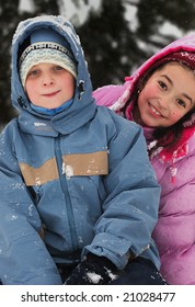 Brother and sister sitting on toboggan in winter