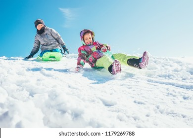 Brother and sister slide down from the snow slope. Winter time pleasures