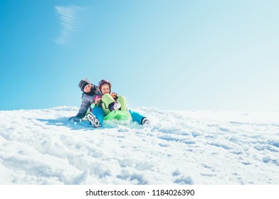 Brother and sister slide down from the snow slope sitting in one slide. Enjoying the winter sledding time