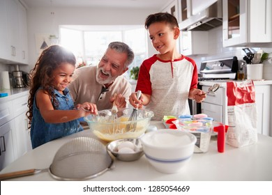 Brother and sister standing at the kitchen table making cake mix with their grandfather, close up