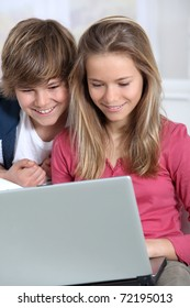 Brother and sister using laptop computer at home