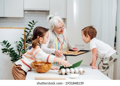 Brother and sister visiting their grandmother, preparing together to put a baking tray with cookies in the oven. High quality photo