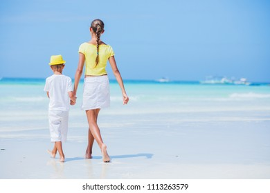 Brother and sister walking and having fun on the beach during the hot summer vacation day.