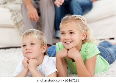 Brother and sister watching television on the floor with their parents in the living-room