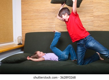 Brother and sister  wearing casual clothes  playing on a green sofa at home fighting with pillows
