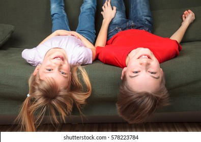 Brother and sister  wearing casual clothes  laying upside down on a green couch at home smiling