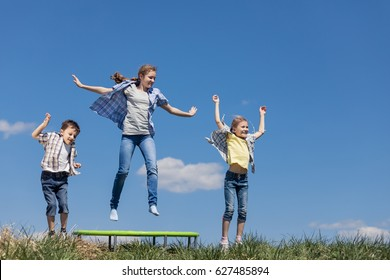 Brother and sisters playing on the field at the day time. People having fun outdoors. They jumping on trampoline on the lawn. Concept of friendly family.