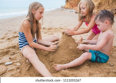 Brother and sisters are playing with sand on the beach. Build castles from sand. Lifestyle photo
