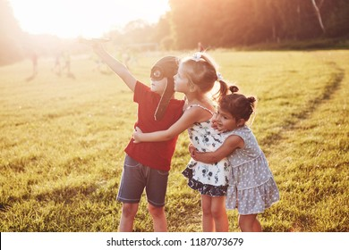 Brother and two sisters are playing together. Three children playing with a wooden airplane outdoor.