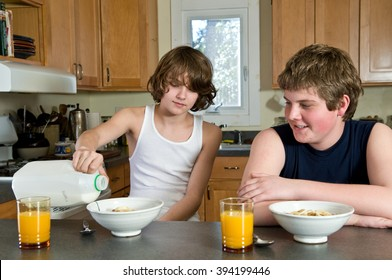 Brothers, ages twelve and fourteen, having fun at breakfast - candid shoot