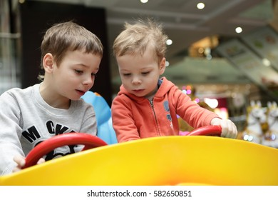 Brothers driving toy car in amusement park