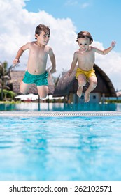 Brothers jumping into the swimming pool