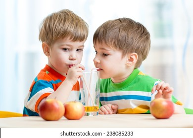 brothers kids drinking juice together from single glass