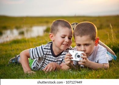 Brothers lying on meadow and taking pic on their camera