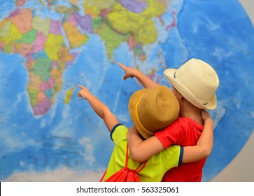 Brothers is playing in travelers. Boys in front of a map of the world. Adventure and travel concept. Creative background....