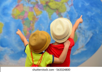 Brothers is playing in travelers. Children in front of a map of the world. Adventure and travel concept. Creative background...