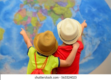 Brothers is playing in travelers. Kids in front of a map of the world. Adventure and travel concept. Creative background.