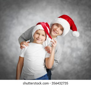 Brothers in Santa hats have fun on grey background