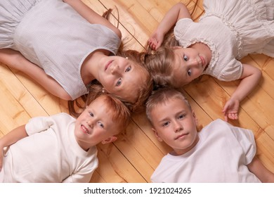 brothers and sisters. 4 children. girls and boys lying on the floor, looking at camera