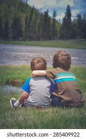 Brothers with their arms around each other looking at a river.
