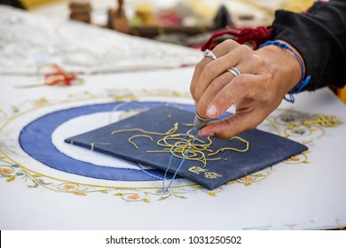 Brouage, France - June 25, 2016 : Closeup of female dressmakers hands doing embrodery work on blue white fabric at Brouage, France.