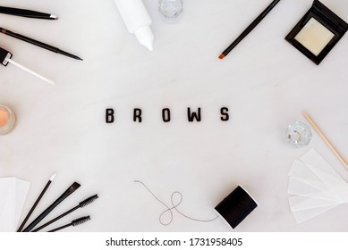 Brow beauty background in a flat lay style with treatment tools, eyebrow makeup and products arranged to create a frame for the word Brows.  Black text on a white background