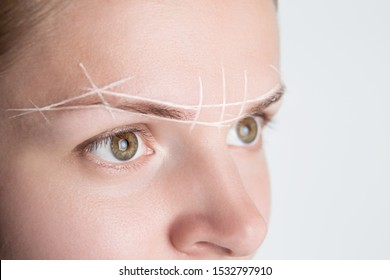Brow marking and measuring before microblading or henna tattoo close-up. White brow paste, threading.