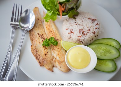 brow rice grilled fish and salad in white dish