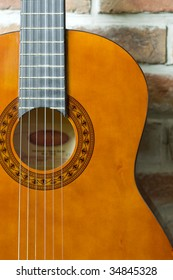 Brown Acoustic Guitar On The Wall Background