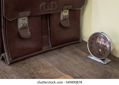 Brown antique schoolbag vintage and vintage clock on old wooden desk. School in the past concept.