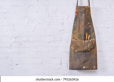 brown apron with paint brushes hanging on white brick wall