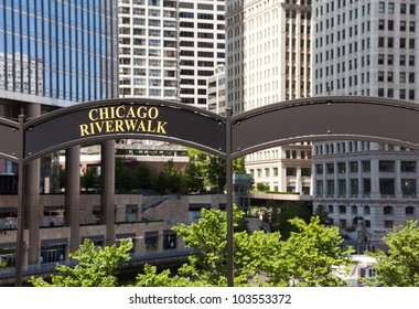 Brown arched sign to Chicago Riverwalk with tribune tower in background