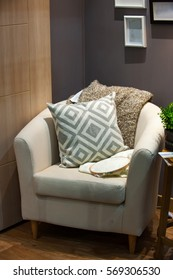 Brown arm chair with a pillow at the corner of the room.