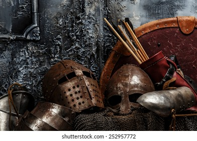 Brown armours. Two helmets, arrows, shield and armours on grey background.